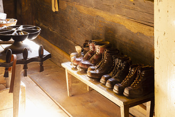 View into a small traditional shoemaker workshop with craft tools, equipment, materials and finished pairs of heavy leather shoes