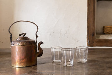 Still life with a beautiful worn retro style copper tea kettle with three empty glasses on a massive wooden table.