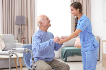 Senior man and young caregiver holding hands indoors