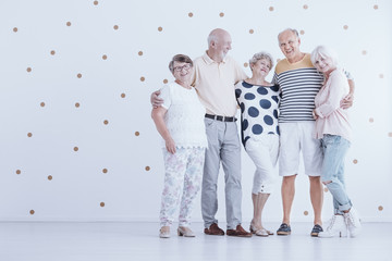 Group of elderly friends hugging each other in white studio with gold dots
