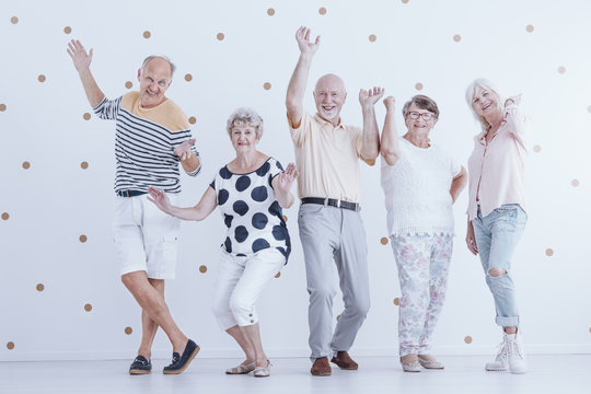 Happy senior people dancing against white background with gold dots