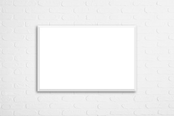 Blank white canvas poster on decorative bricks wall