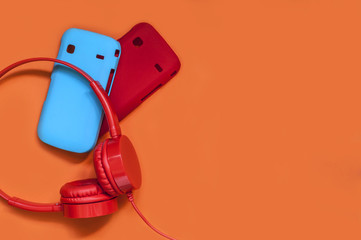 bright headphones and covers for the phone on an orange background