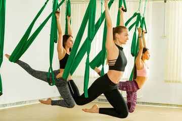 Young women performing aerial yoga exercise