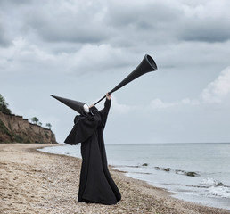 Strange figure in black cloak with the mirror face in seaside. Blowing to the big tube.