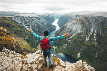 Happy Man backpacker on mountain summit traveling in Norway Lifestyle Travel adventure active vacations above Naeroyfjord success wellness healthy life concept