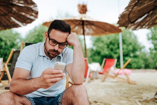 Annoyed man on the beach looking at the mobile screen.