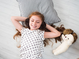 Top view of  kid with pillow and doll on the floor.