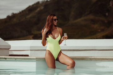 Woman relaxing in pool with wine