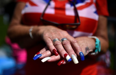 A woman wearing a Union Flag top shows of her manicure a day before the wedding of Prince Harry and Meghan Markle, in Windsor