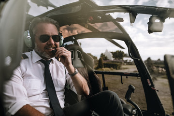 Happy helicopter pilot talking on headset