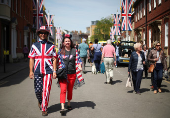 A couple wearing Union Flag and U.S. flags hold hands near Windsor Castle a day ahead of Prince Harry's and Meghan's Markle's wedding, in Windsor