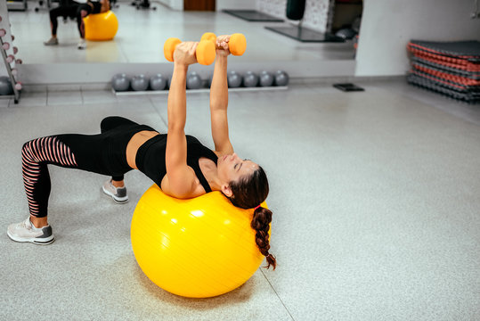 Girl exercising on yellow gym ball and dumbbells.