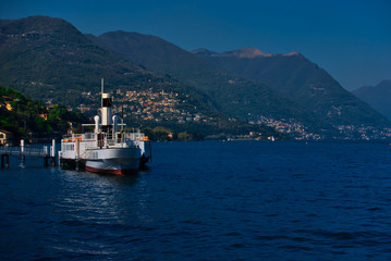 Boat for public navigation moored on the lakefront of Como, Italy.