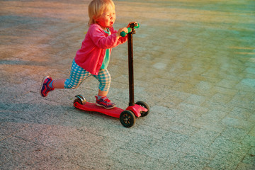 little girl riding scooter outdoors, active kids