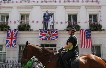 Police officer on horseback, rides past a cutout of Prince Harry and Meghan Markle, ahead of their wedding, in Windsor