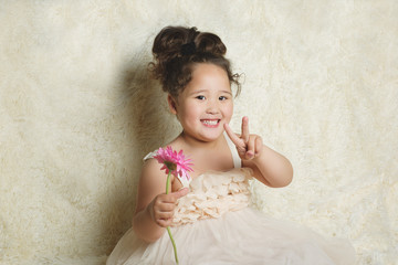Pretty little curly girl with pink flower