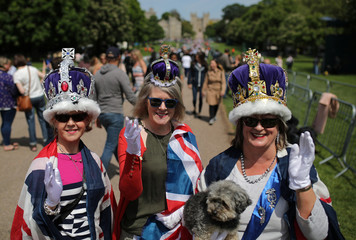 Fans of the Royal family wear crowns and the British flag as they pose for pictures on the Long Walk in Windsor