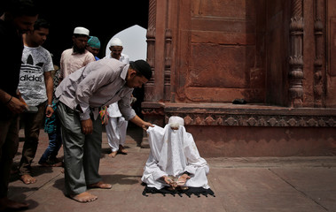 A man begging for money while posing as a woman is confronted inside Jama Masjid (Grand Mosque) on the second day of Ramadan in the old quarters of Delhi