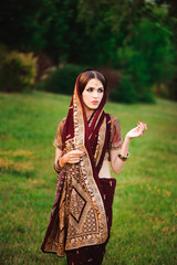 Beautiful Arabian woman portrait. Young Hindu woman with mehndi tattoos from black henna on her hands.