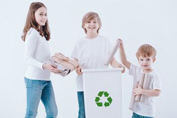 Smiling kids segregating paper waste