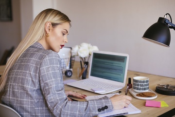 Young businesswoman working in office, using laptop