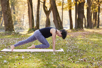 Mid adult woman in forest practicing yoga, climber exercise