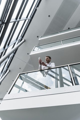 Businessman in office building leaning on railing looking at cell phone