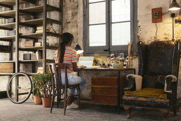Back view of young woman sitting at desk in a loft working on laptop