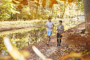 Couple jogging on autumnally forest track