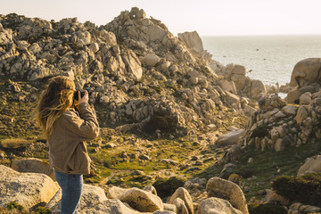 Italy, Sardinia, woman on a hiking trip taking a picture at the coast