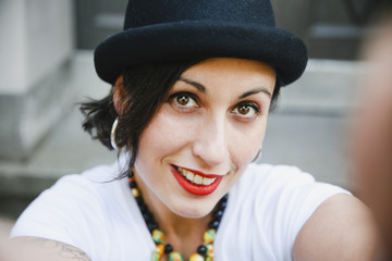 Portrait of smiling woman with hat taking selfie