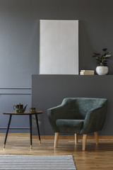 Green armchair next to black table in grey apartment interior with mockup of empty poster