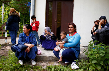 Migrants sit near a bus after it was stopped and turned back by the police, near Konjic