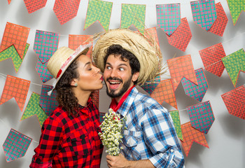 Festa Junina: party in Brazil. Man and woman dressing checked pattern clothes. Woman kissing boyfriend.