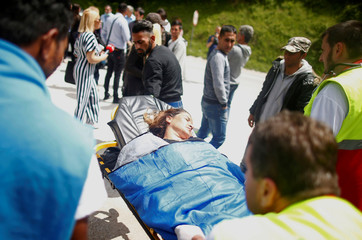 Emergency workers help the migrants who got sick after their bus was stopped and turned back by the police, near Konjic