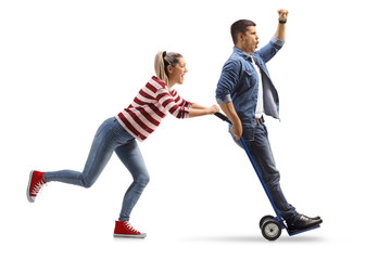 Young woman pushing a hand truck with a young man riding on it