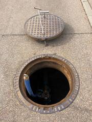 Fotobehang Kanaal Offener Schacht zu einer Wassertechnischen Einrichtung auf einer Straße