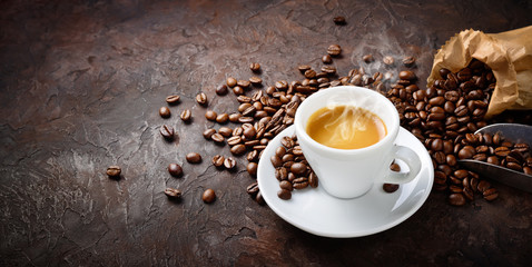 Espresso and coffee beans on plaster background