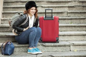 Giovane turista seduta in una scala con la valigia rossa ha un espessione di disagio