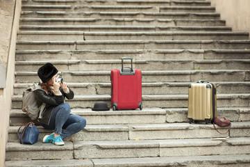 Turistaurista seduta in una scalinata con la valigia rossa