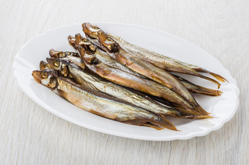 Heap of smoked capelin in oval dish on table