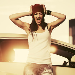 Young angry fashion hipster woman in white tank top screaming beside her car