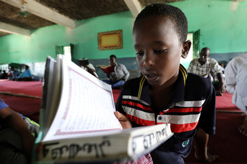 A Muslim boy reads the Koran before the start of the Friday prayers during the holy fasting month of Ramadan inside a Mosque in Mogadishu