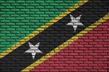 Saint Kitts and Nevis flag is painted onto an old brick wall