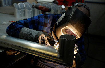 A worker welds the aluminium part of a goal at Interplastic, a Polish manufacturing company who are supplying the football goalposts for the 2018 World Cup finals in Russia, in Chwaszczyno
