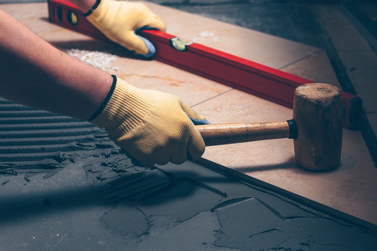The working tiler knocks on the tile with a Tile Mallet, the professional checks the building level