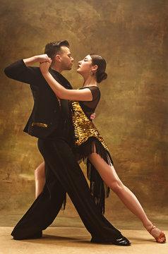 Dance ballroom couple in gold dress dancing on studio background.