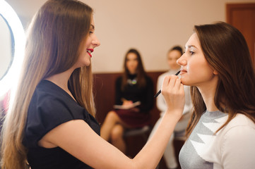 Makeup artist creating beautiful makeup for brunette model