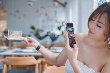 Closeup of asian women taking photo of sweet dessert by smartphone at coffee cafe.